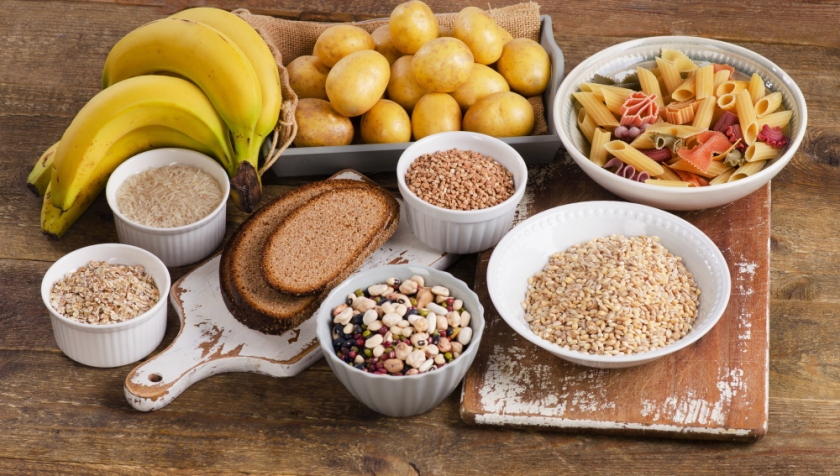 Foods high in carbohydrate on wooden background.